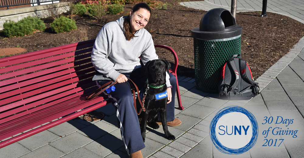 Female student at SUNY Delhi sits with a seeing eye service dog on a bench outside.