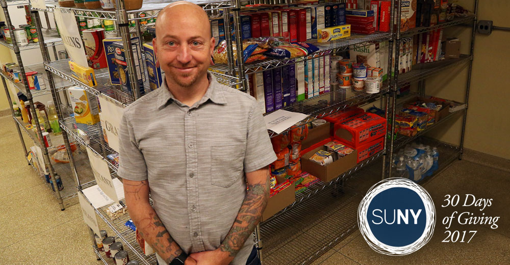 A male staff member stands in front of a shelf full of food products in the Dutchess Community College food pantry.