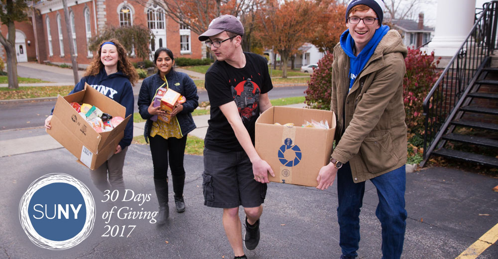 SUNY Geneseo students carry boxes of food and non-perishable items up a driveway.