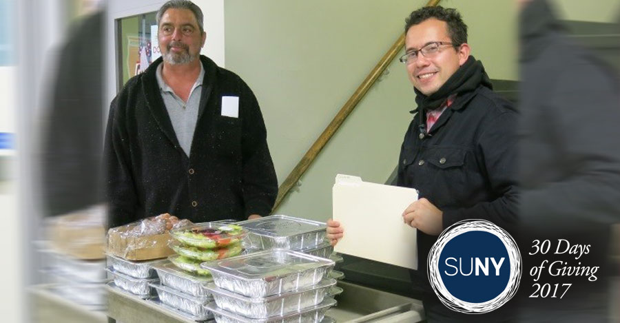 A male student and male staff member from Mohawk Valley Community College stand behind prepared meal packages ready to donate to food banks.