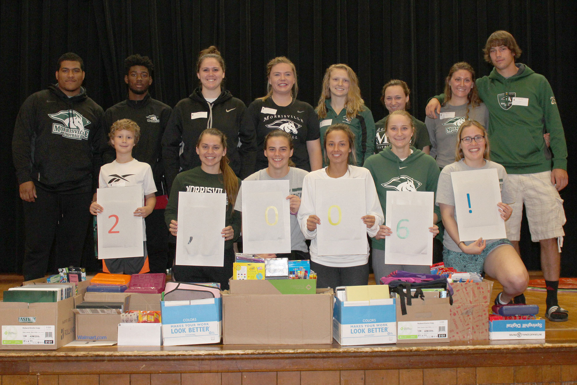 Athletes from SUNY Morrisville pose with elementary school students during a back to school celebration.