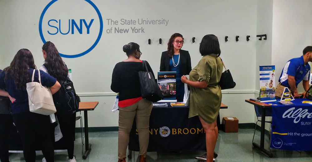 Students talk to college representatives at the SUNY-EOC Community College Fair in Brooklyn.