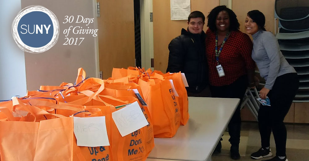Westchester Community College students stand behind a table of orange bags filled with food donations.