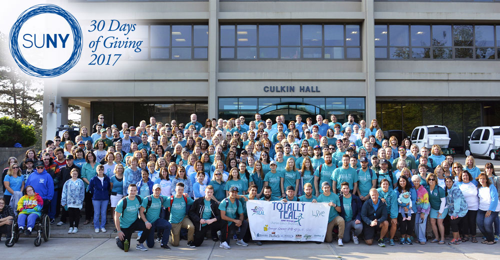 Participants pose in front of Culkin Hall at SUNY Oswego on Teal Day.