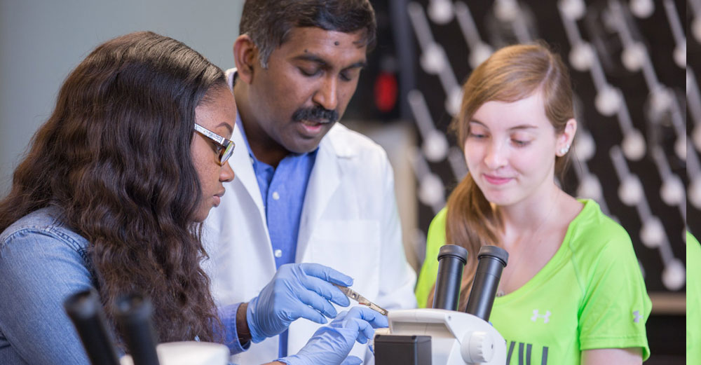 A middle eastern professor works with 2 female students behind a microscope.