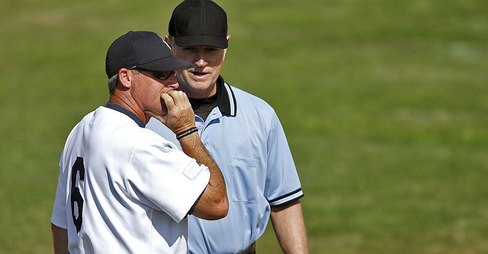 A baseball coach talks to an umpire on the field.