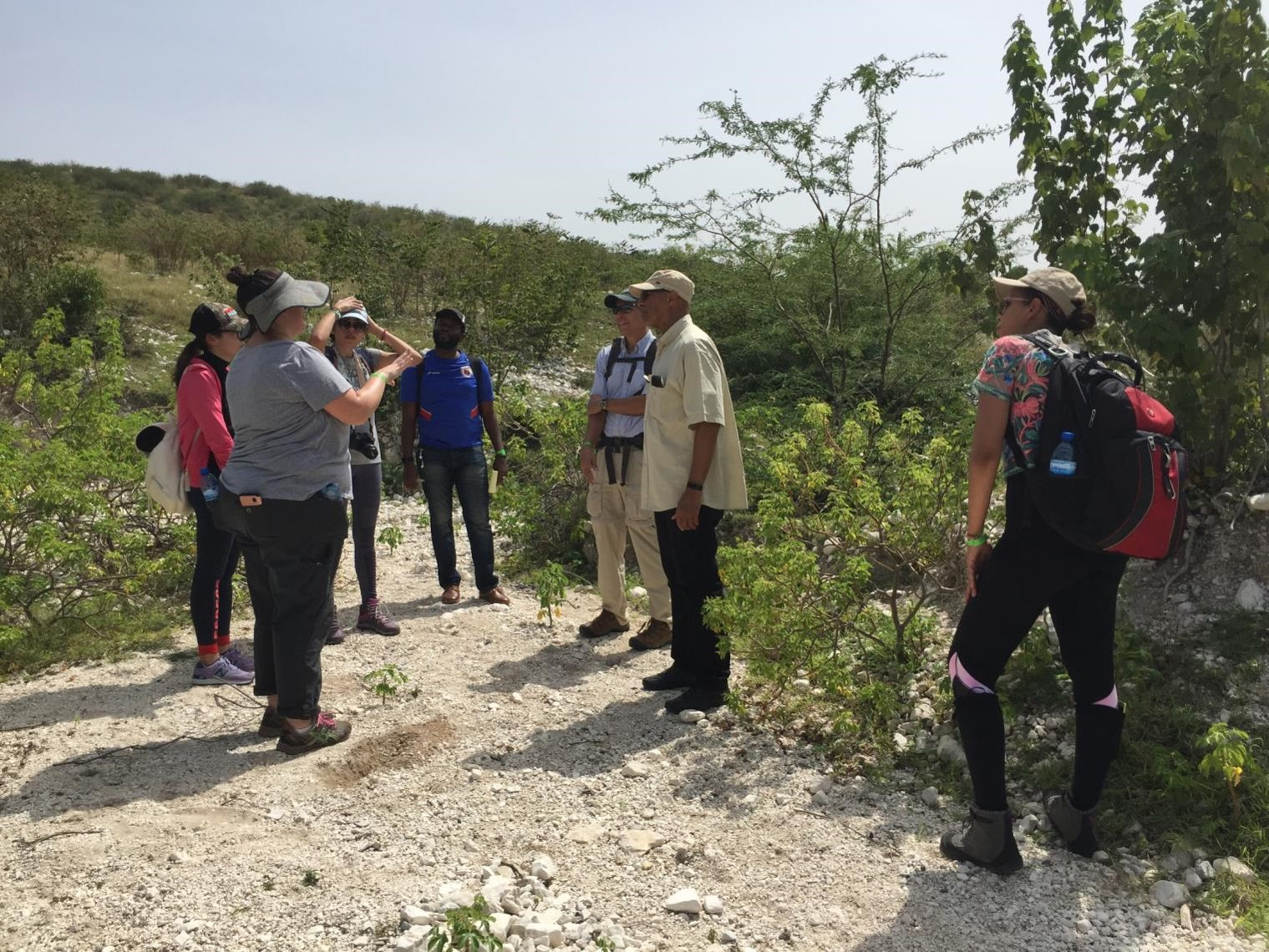 Graduate students from SUNY ESF stand on a gravel path talking with colleague Professor Emanuel Carter in Haiti.