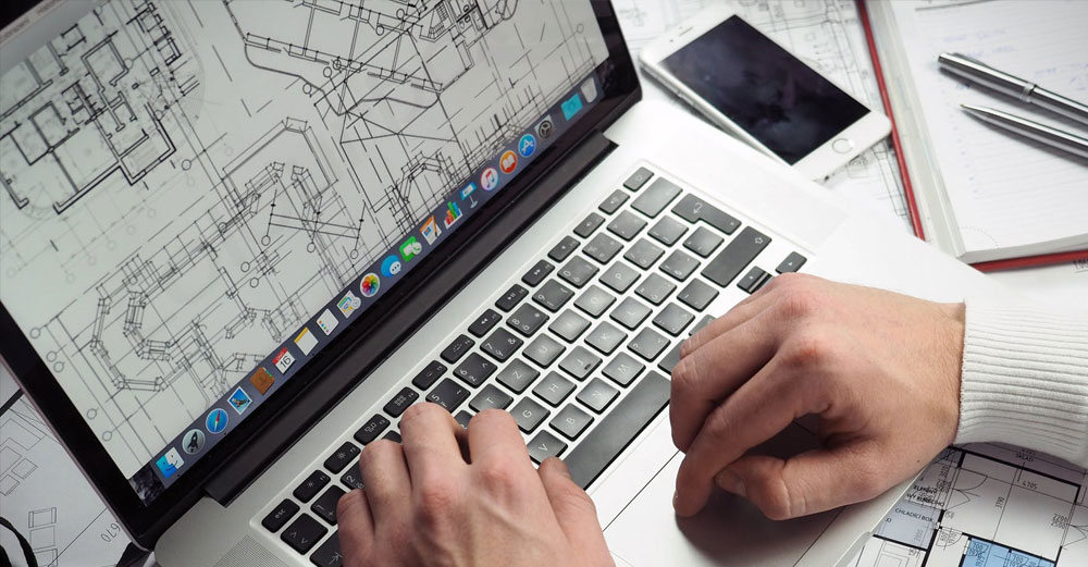 Someone works on construction blueprints on a laptop computer.