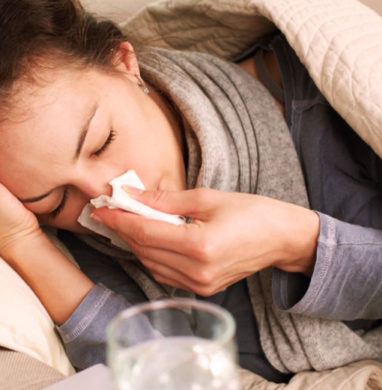 Woman lies in bed under blankets blowing her nose.