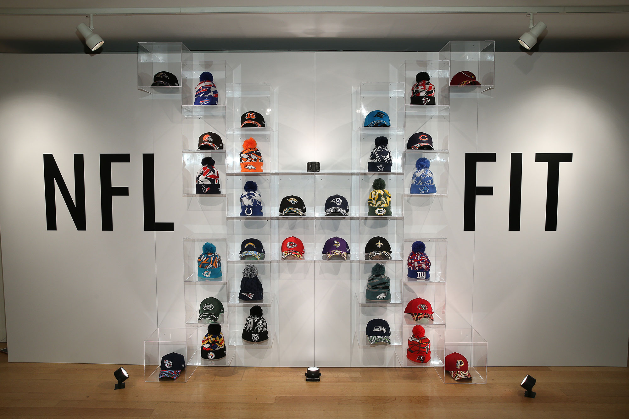 Hats of NFL teams set up in cases making an X to form NFL xFIT display.