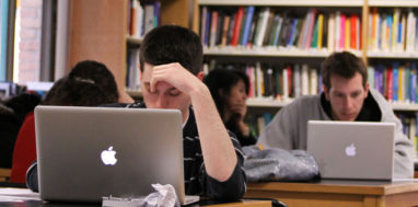 Student looks down and stressed outwith his hand holding his head up in the library.