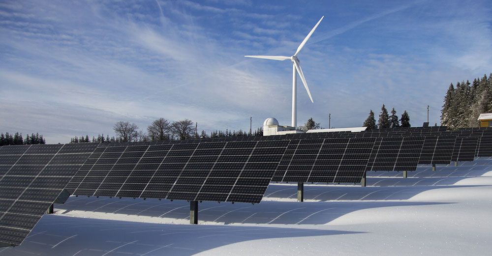 A windmill stands behind a field of solar panels in the winter snow.