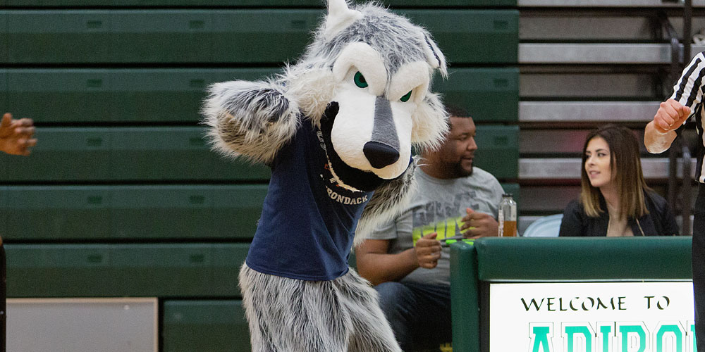 SUNY Adirondack Community College mascot Eddie Rondack dances at a basketball game.