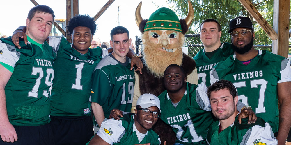 HVCC mascot Viking with football players around him.