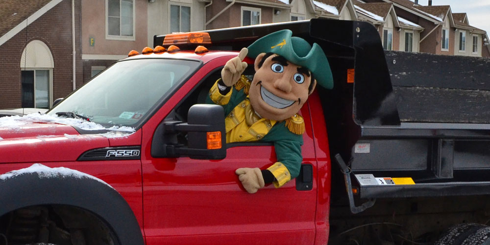 Herkimer County Community College mascot General Herkimer leans out the driver's seat of a snow plow.