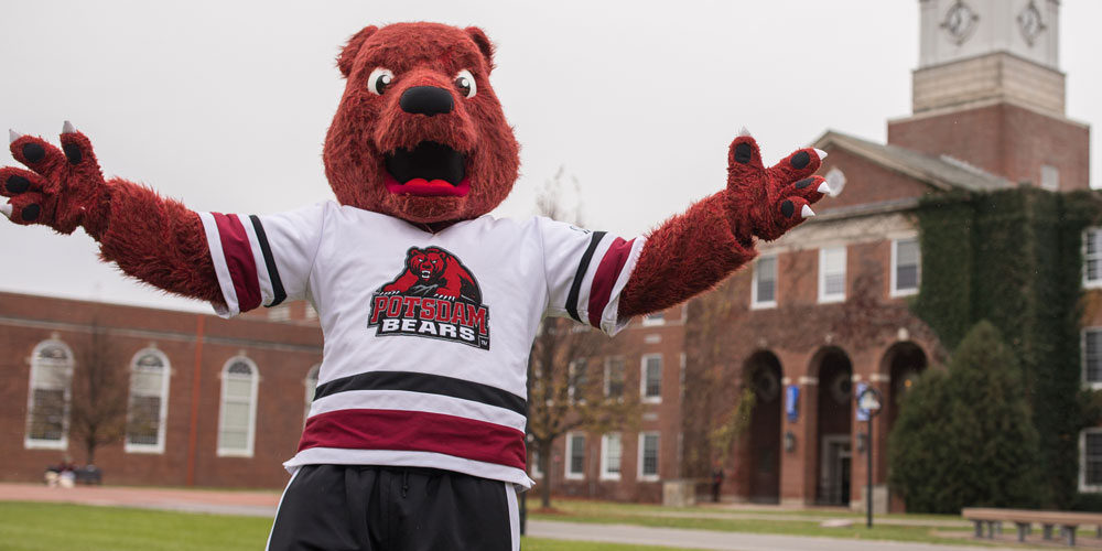 SUNY Potsdam mascot Max C Bear stands with arms outstretched in front of campus building.