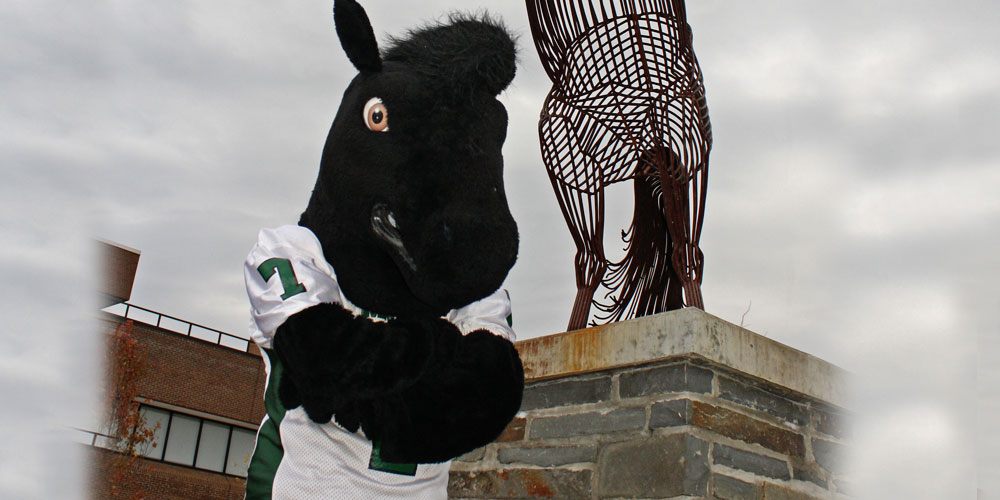 Morrisville State College mascot Mustang outside in front of horse statue.