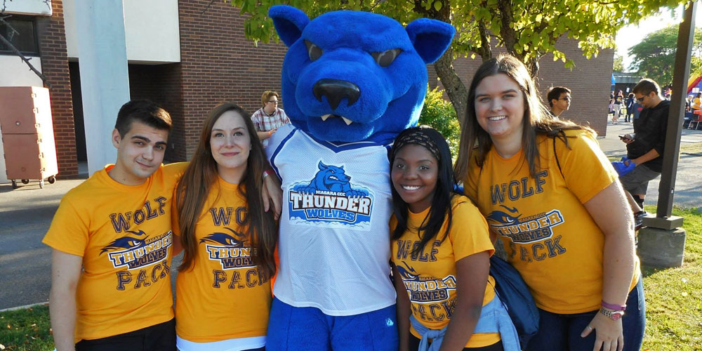 Niagara County Community College mascot Tripp with student life volunteers outside.