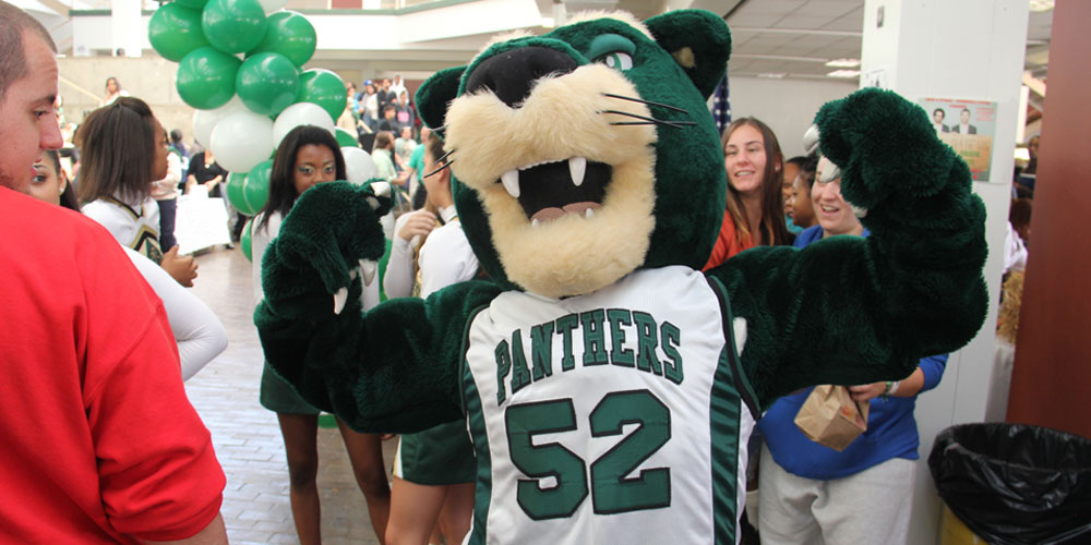 SUNY Old Westbury mascot OWWIN stands with arms flexing.