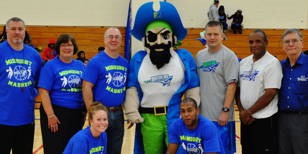 Fulton-Montgomery Community College's Reggie Raider mascot with people on a basketball court.