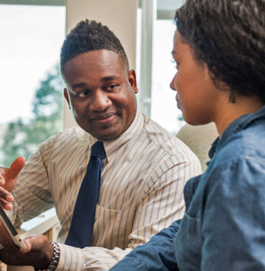 A counselor speaks to a female student about financial aid at his desk in his office.