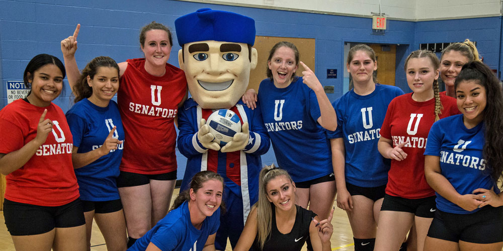 SUNY Ulster mascot Senator Sam stands with the women's volleyball team.