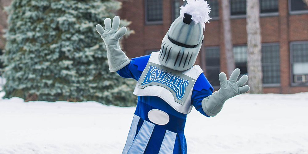 SUNY Geneseo's mascot Victor E Knight outside in front of the Suess spruce tree.
