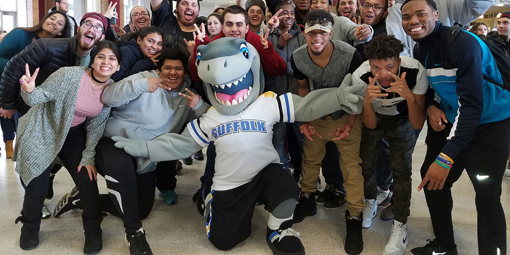 Suffolk Community College mascot Finn the Shark kneels with students all around.