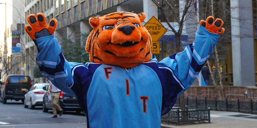 FIT mascot Stitch the Tiger stands in NYC street with arms outstretched.