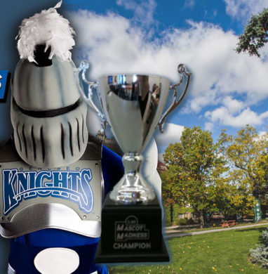 Victor E Knight of SUNY Geneseo stands with Mascot Madness trophy, over a picture of the SUNY Geneseo suece spruce tree.