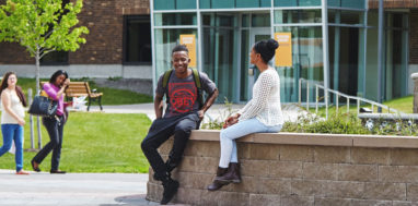 Students sit outside on a stone wall at Onondaga Community College.