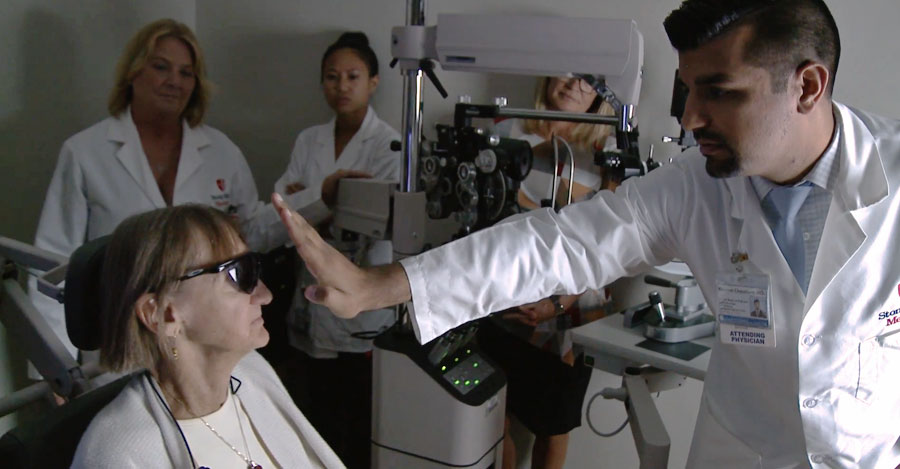 A male doctor works with an old, female patient as she tests a bionic eye that will allow her to process light and dark.