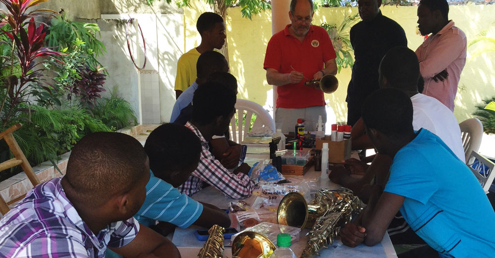 Bill Cole shows Hatian locals the details of a horn as musical instrument.