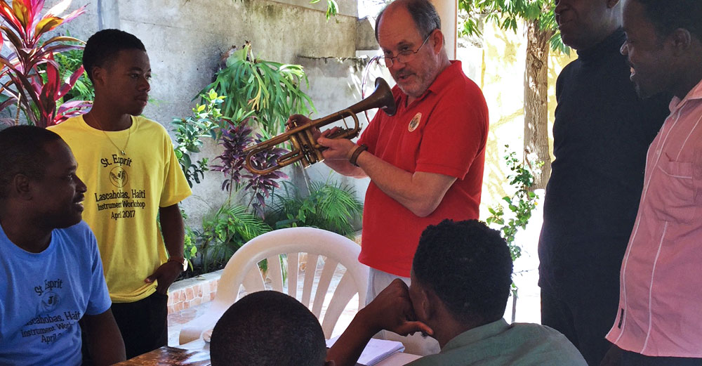 Bill Cole holds up a woodwind horn as he teaches locals in Haiti about it.
