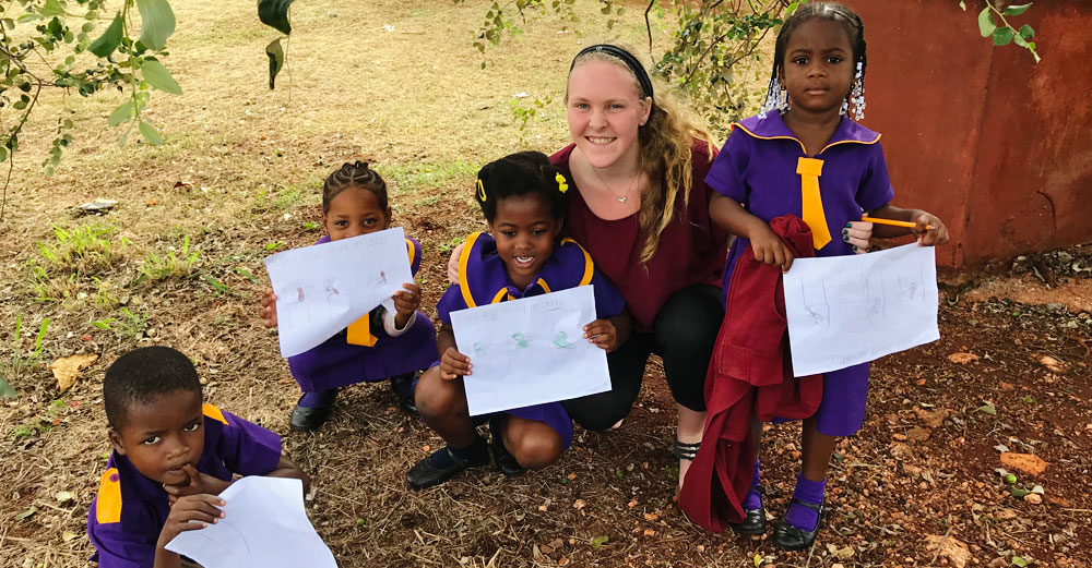 Farmingdale State College student Kaitlyn Kallansrude outside with school children in Jamaica.
