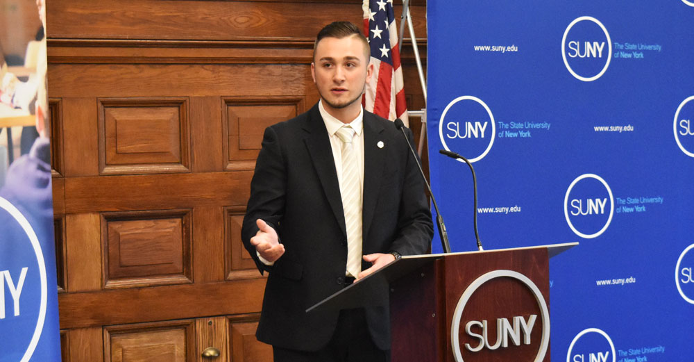 SUNY Student Assembly president Michael Braun speaks at podium.