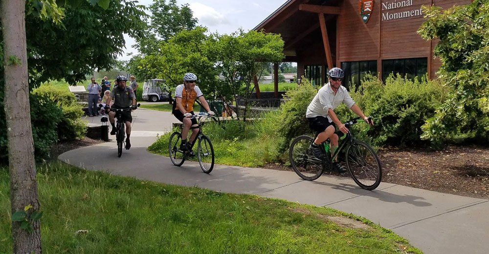 People ride bikes near the Fort Stanwix museum on the Mohawk Valley Region Path Through History.