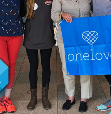 A group of women stand holding a OneLove banner before walking iin a Yards For Yeardley event.