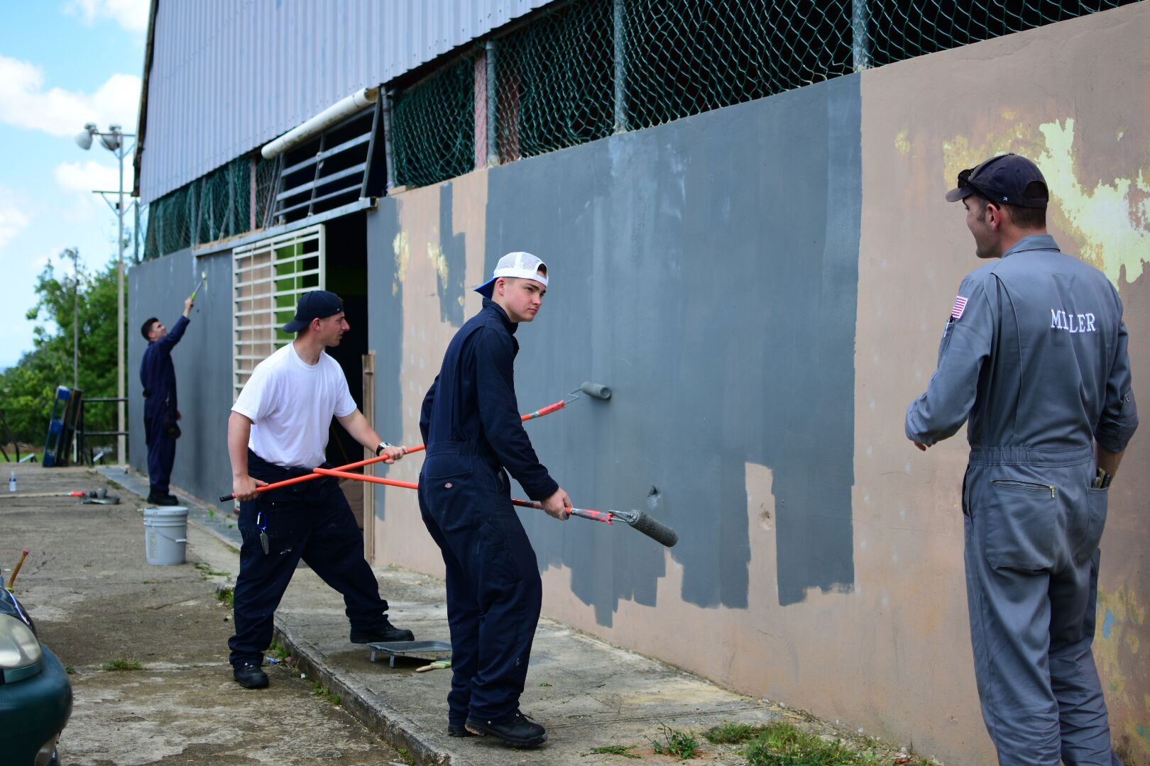 SUNY Maritime College students paint a building exterior in Puerto Rico.
