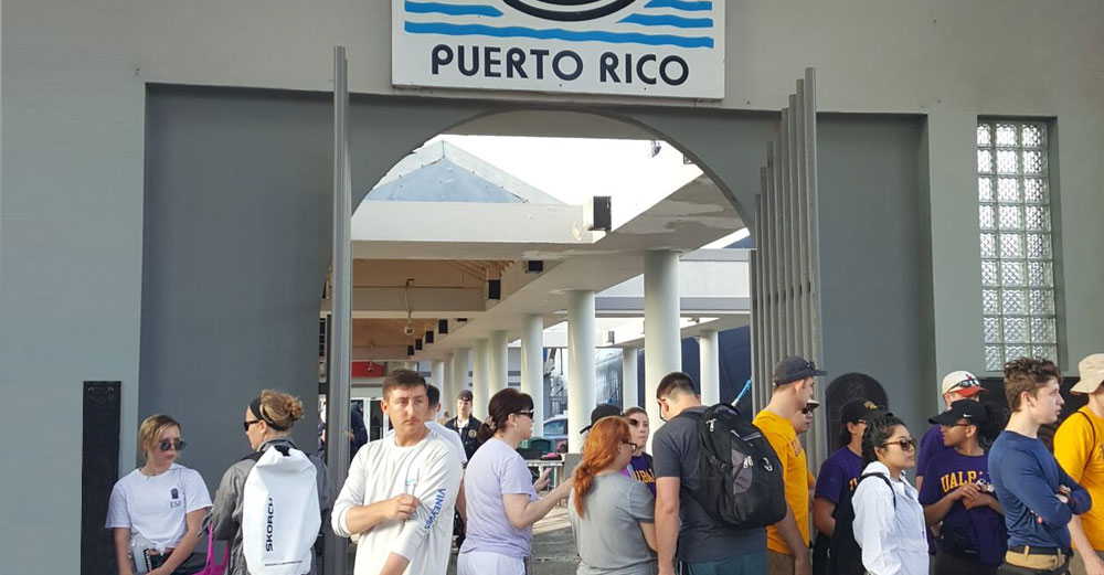 SUNY students stand on a pier after reaching the island of Puerto Rico for their recovery mission.