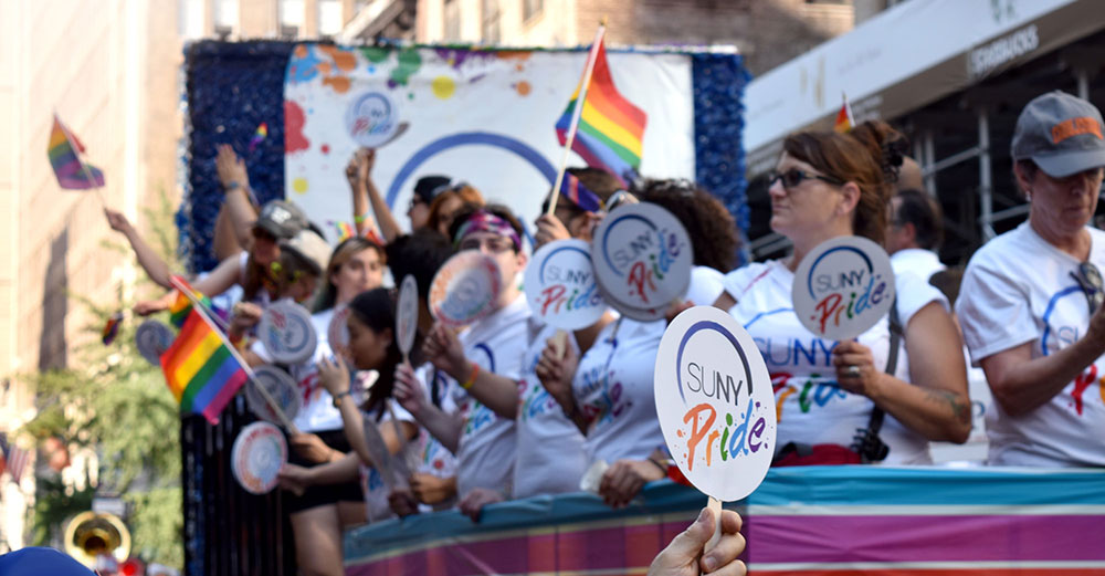 A parade float with SUNY Pride banner and people waving rainbow flags on it.