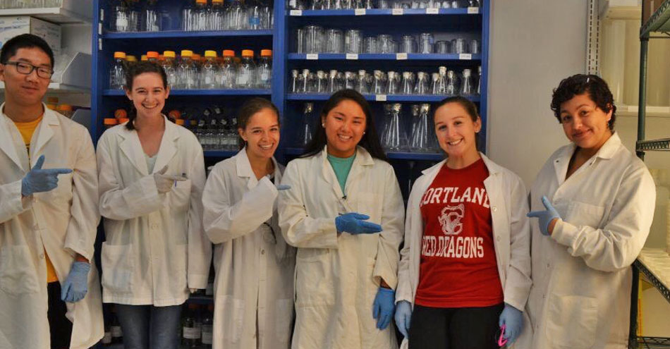 A girl in Cortland Red Dragons tshirt stands among others in white lab coats in a science lab.
