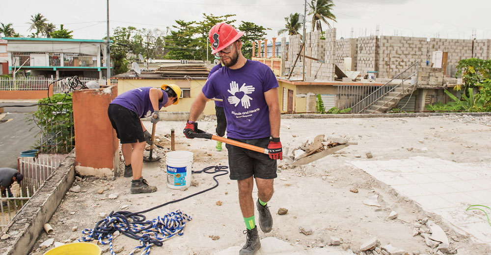 SUNY College at Brockport student shovels debris off a roof in Puerto Rico.
