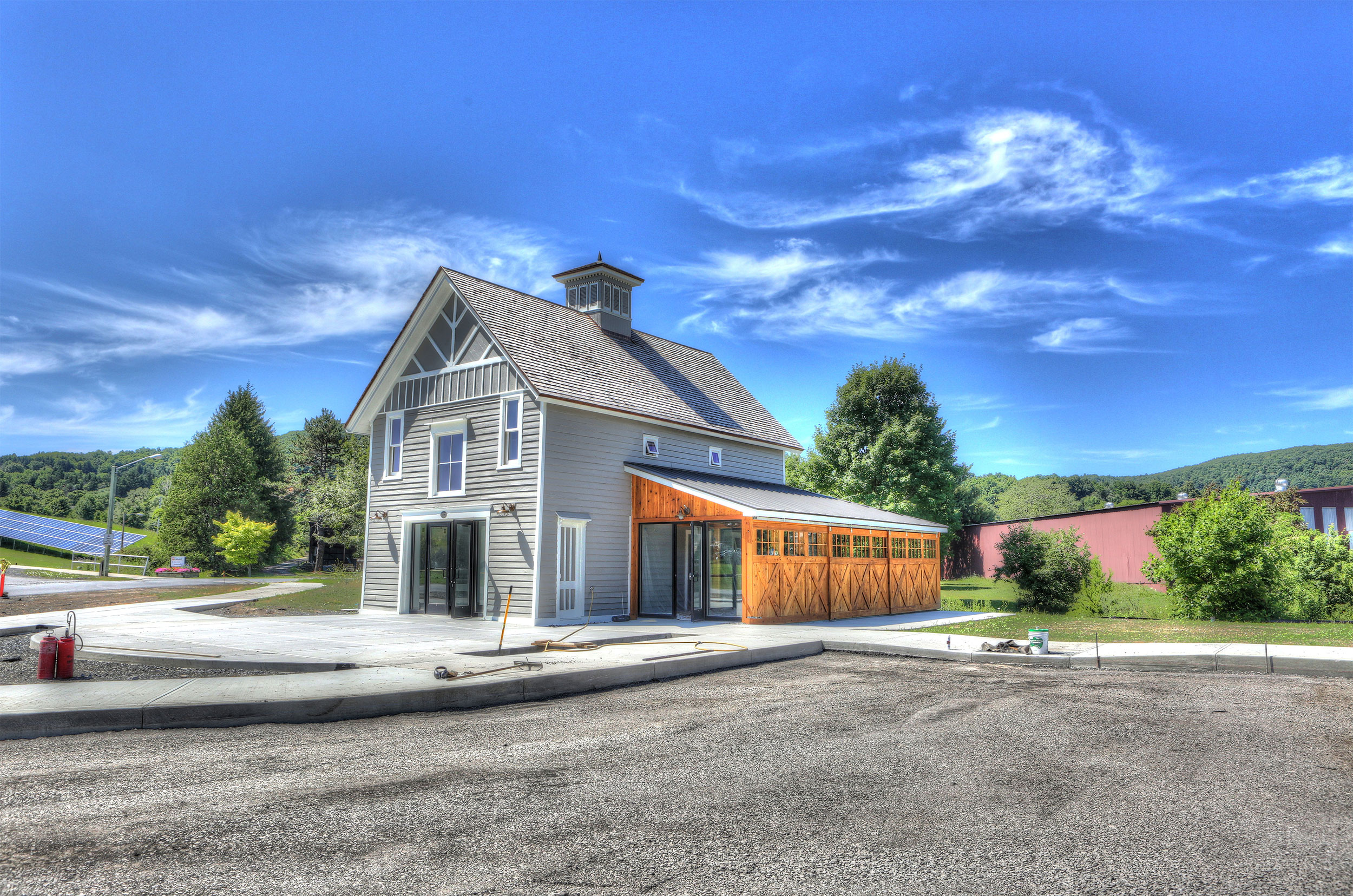 Coblsekill cafe and general store exterior with solar panels on the grass to the left side.