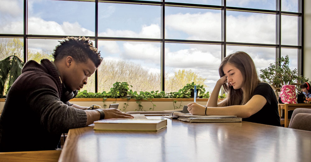 Male and female students at Finger Lakes Community College study at table in front of windows.