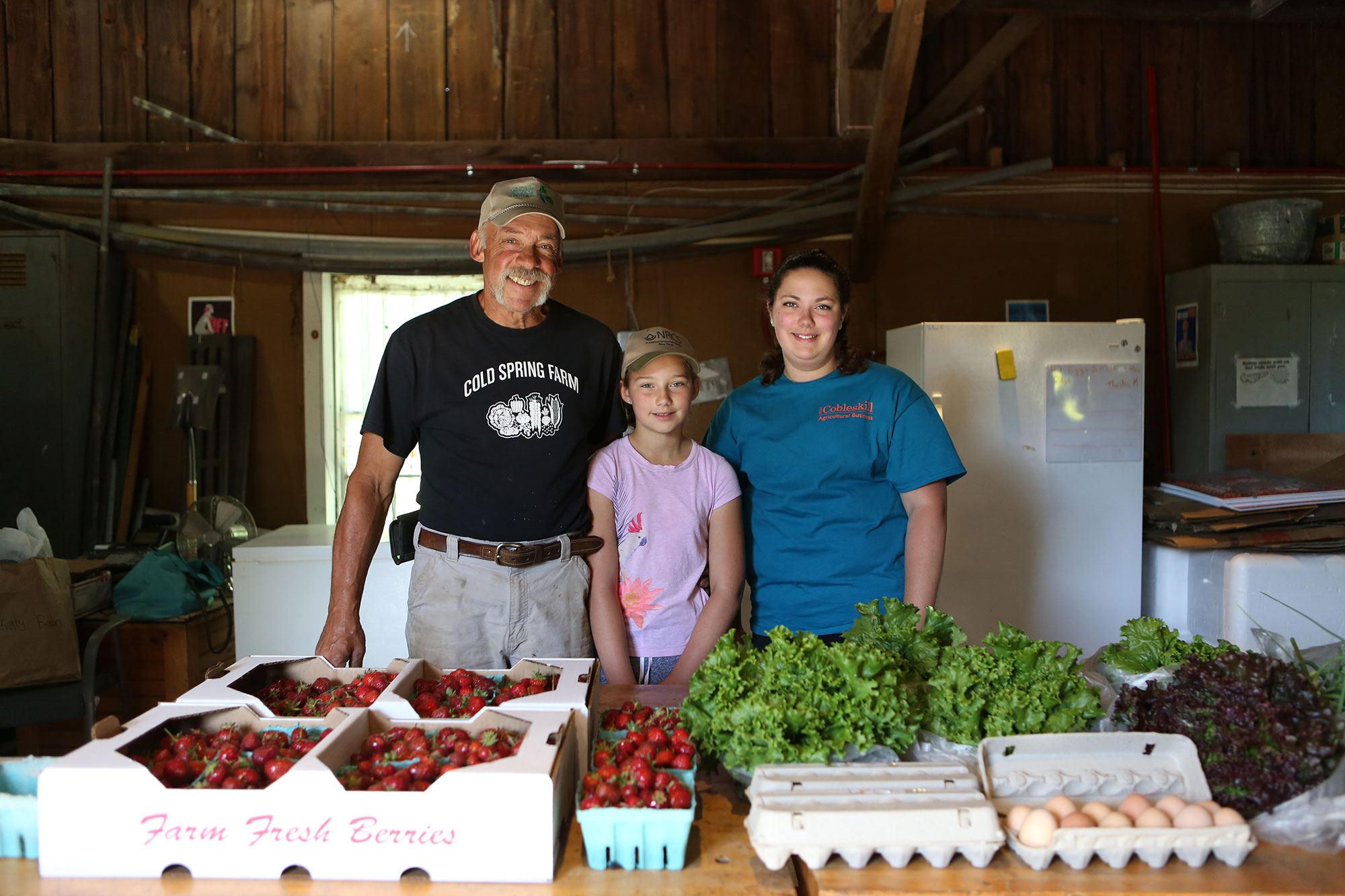 3 people stand behind a table of fresh produce and eggs being sold at the Scoharie Fresh General Store.