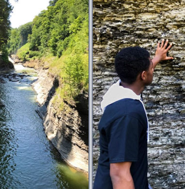 2 male EOP students from Monroee Community College touch rock wall formation at Letchworth State Park.
