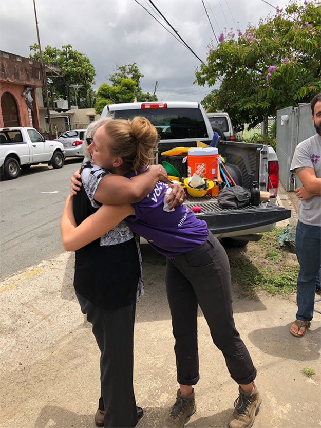 A SUNY student hugs a local resident after completing work for the day.