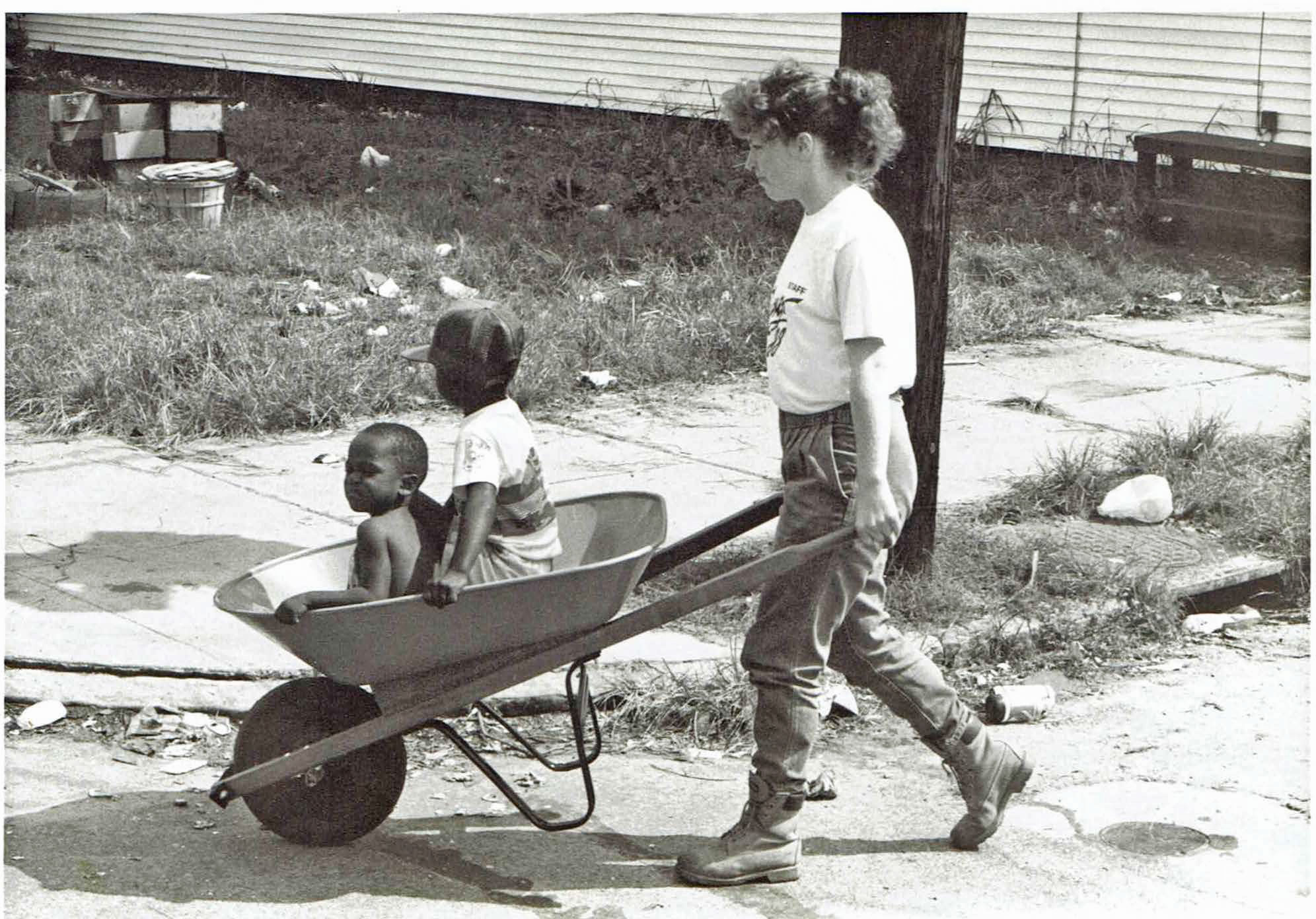 In 1989, a female SUNY Delhi volunteer pushes children to saefty in a wheelbarrow in hurricane damagaed Charleston, South Carolina.