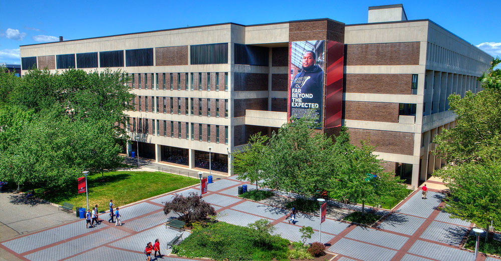 Stony Brook University campus building aerial photo with students walking outside.